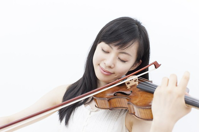 young woman joyfully playing a violin