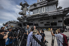 Rear Adm. John Fuller, commander of Carrier Strike Group 1, left, and Capt. Doug Verissimo, commanding officer of USS Carl Vinson (CVN 70), address the media after pulling into Naval Base Guam. (U.S. Navy/MC3 Dylan M. Kinee)