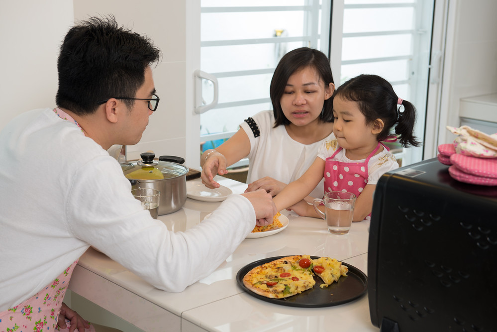 asian family enjoying and cooking pizza