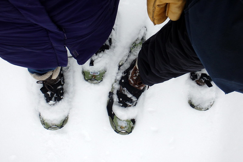 Selfie of the bottom half of two people wearing snowshoes.
