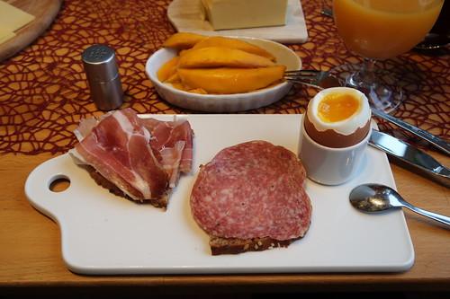 Fenchelsalami und luftgetrockneter Schinken (vom Sattelschwein) auf Saatenbrot zum Frühstücksei - außerdem frische Mango