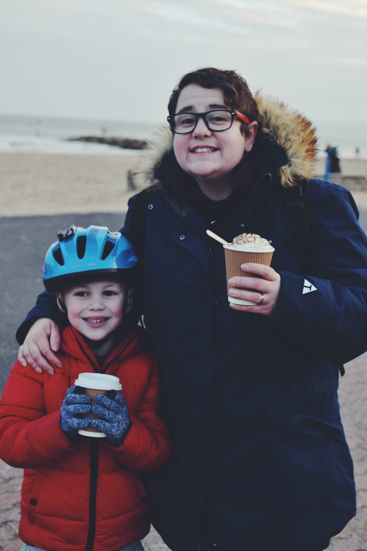 Smiling on the beach with hot chocolates