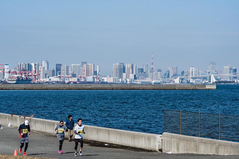 海をバックに走るマラソンランナーたち