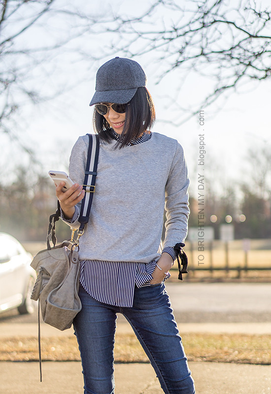 gray baseball cap, gray sweatshirt with ribbon ties, navy striped button up shirt, gray tote with striped strap, skinny jeans