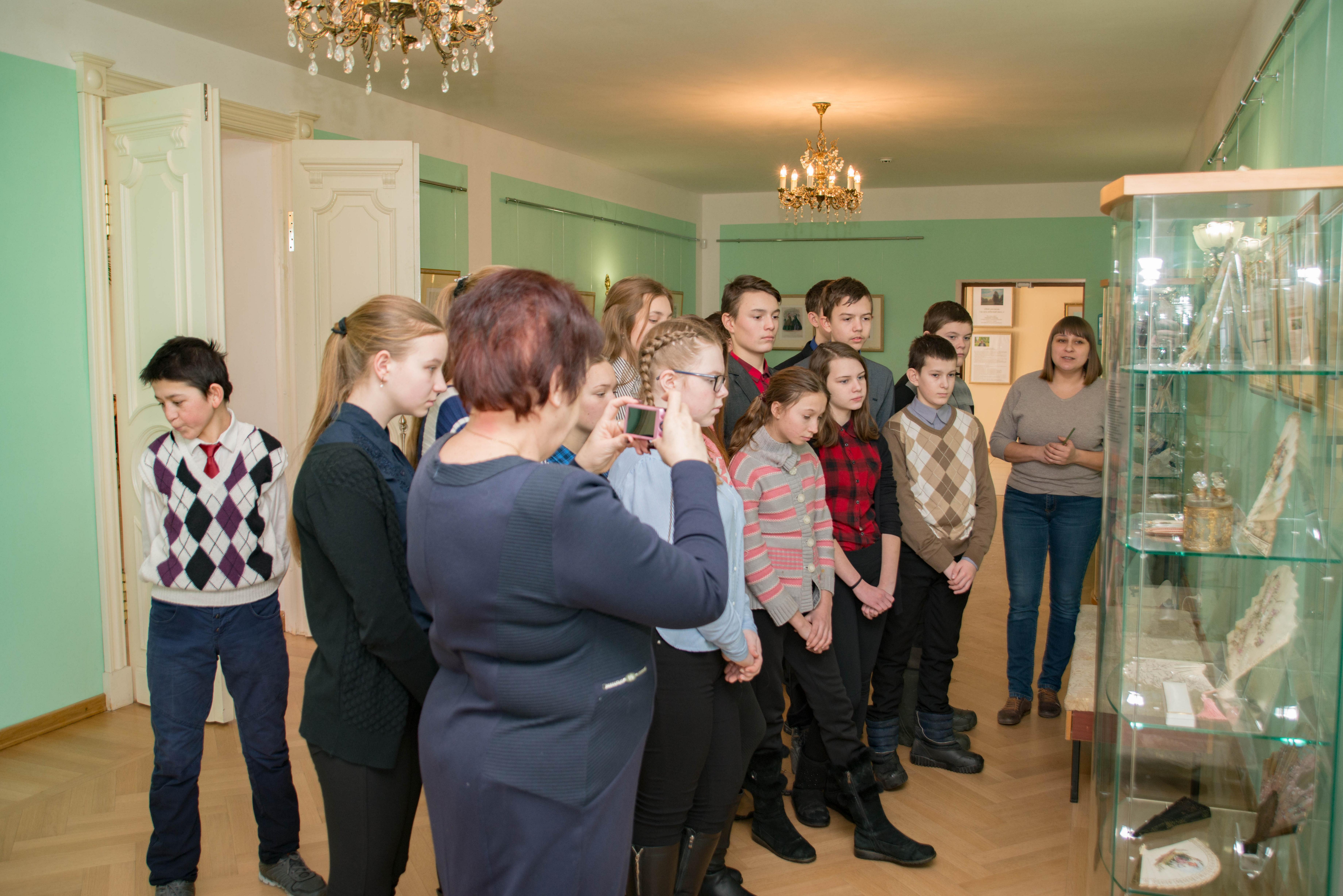 Экспозиционер Савочкина Е. со школьниками на выставке«Наряды необходимы счастью женщины, как цветы весне...»
