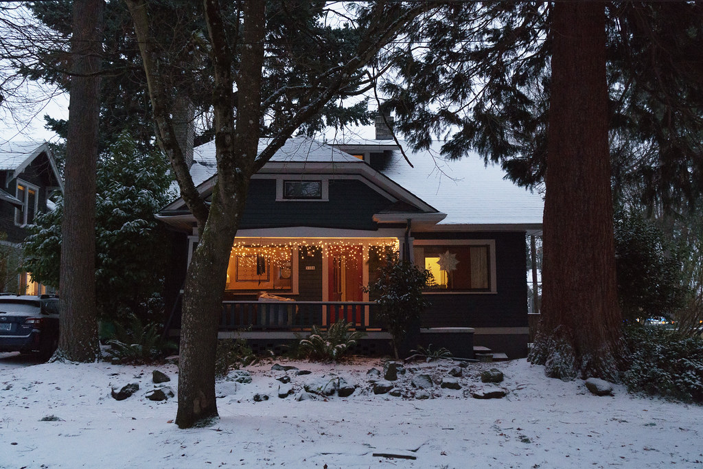 A house with Chritmas lights on a snowy Christmas Eve in the Irvington neighborhood of Portland, Oregon