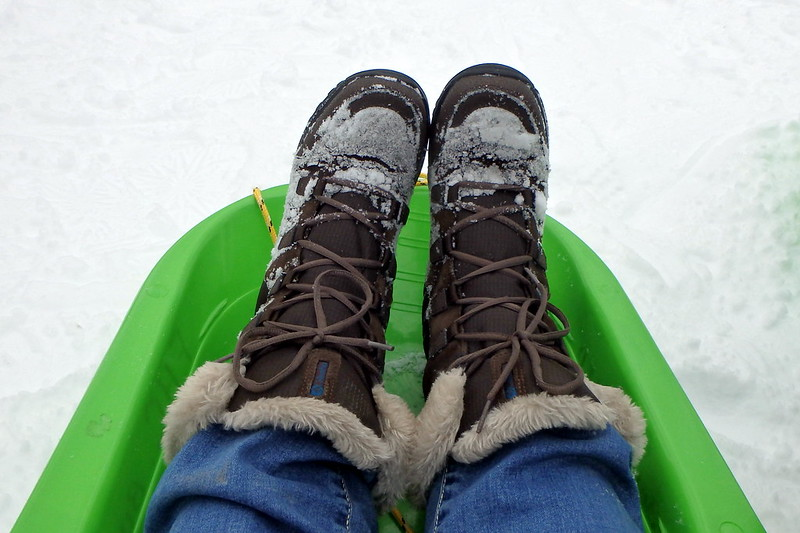 Selfie that is simply two boots in a bright green sled.