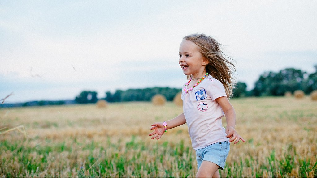A young girl running in a field