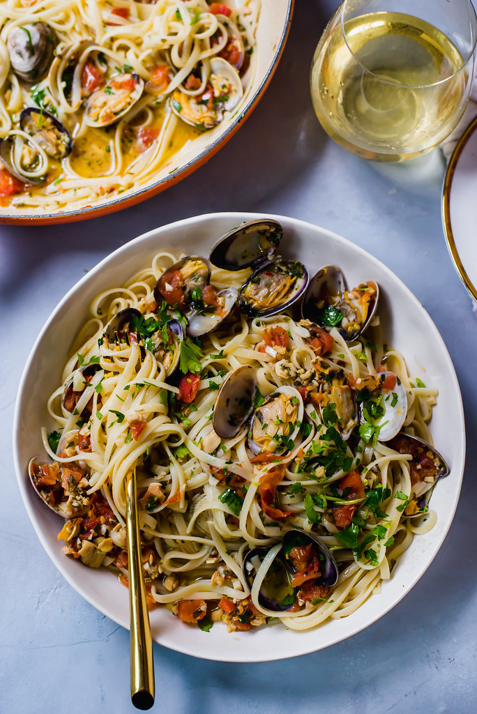 Classic linguini and clams recipe with a touch of white wine, tomatoes for sweetness and a gorgeous garlic sauce that wraps around each pasta strand.
