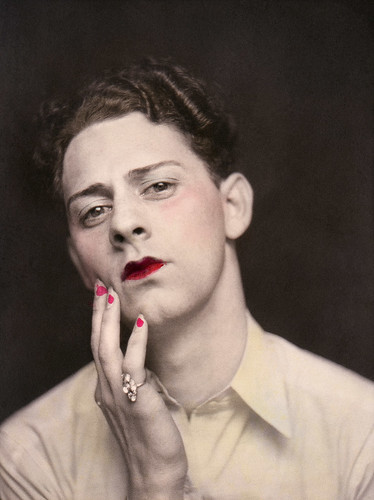 Man in makeup wearing ring. Photograph from a photo booth, with highlights of color. United States, circa 1920. © Sebastian Lifshitz Collection Courtesy of Sebastian Lifshitz and The Photographers' Gallery