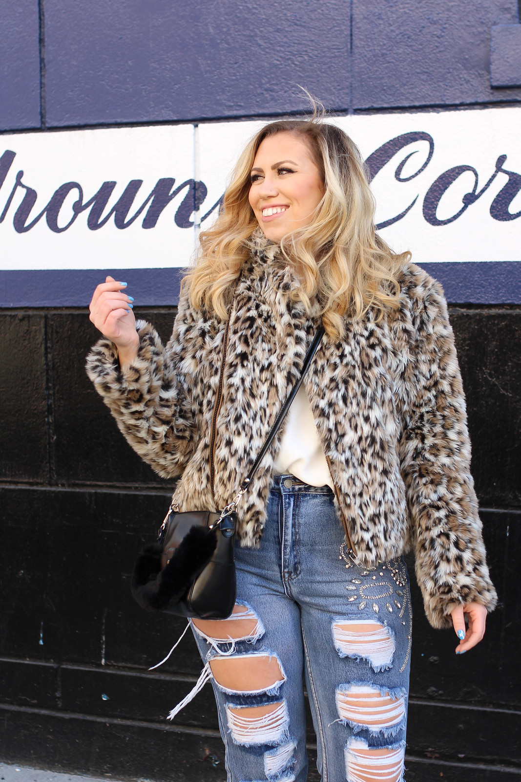 Blonde Girl Smiling In Leopard Coat And Distressed Jeans