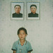 Polaroïd of a North Korean girl posing below the portraits of the Dear Leaders inside her home, South Pyongan Province, Chonsam Cooperative Farm, North Korea