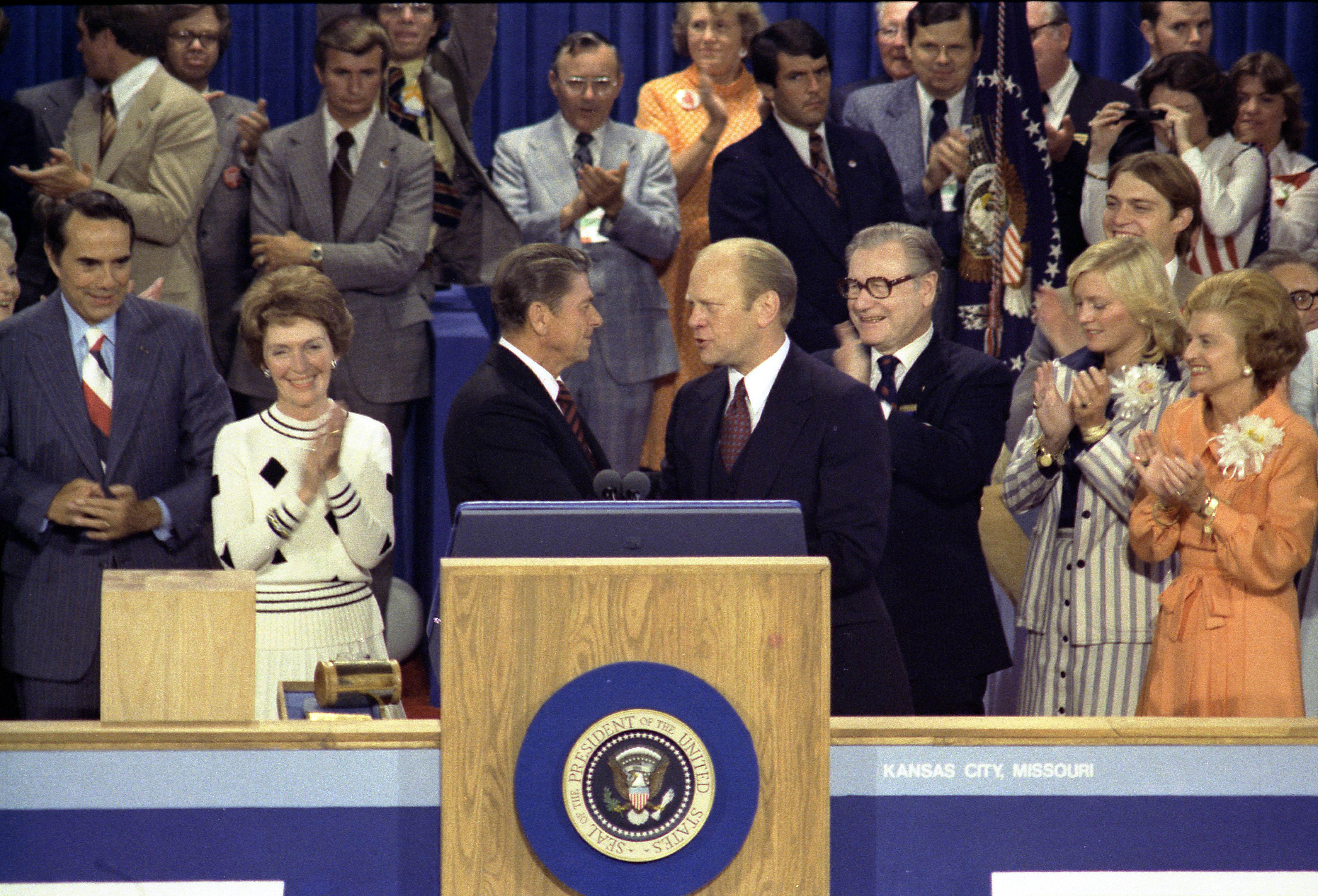 On the podium with Gerald Ford after narrowly losing the nomination at the 1976 Republican National Convention. President Gerald Ford, as the Republican nominee, shakes hands with nomination foe Ronald Reagan on the closing night of the Convention at Kemper Arena in Kansas City, Missouri, August 19, 1976. Vice-Presidential Candidate Bob Dole is on the far left, then Nancy Reagan, Governor Ronald Reagan is at the center shaking hands with President Gerald Ford, Vice-President Nelson Rockefeller is just to the right of Ford, followed by Susan Ford and First Lady Betty Ford.