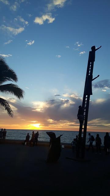 Statue of children climbing a ladder at sunset