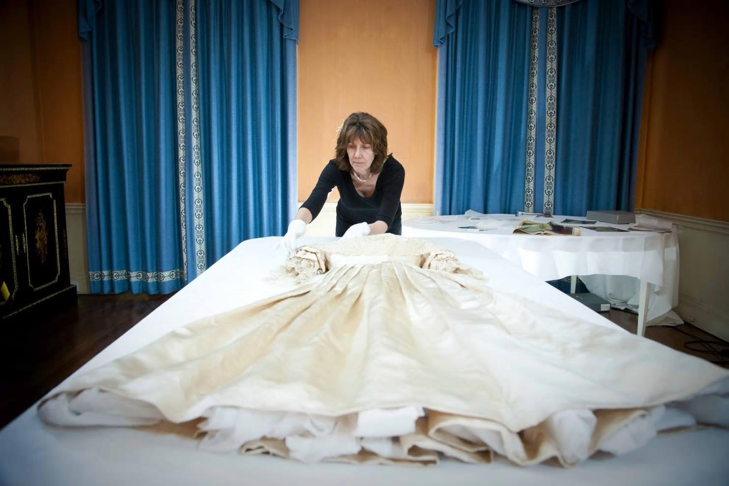 The silk satin wedding dress worn by Queen Victoria in 1840, when she married Albert Saxe-Coburg, is prepared by a conservator for conservation work to begin.
