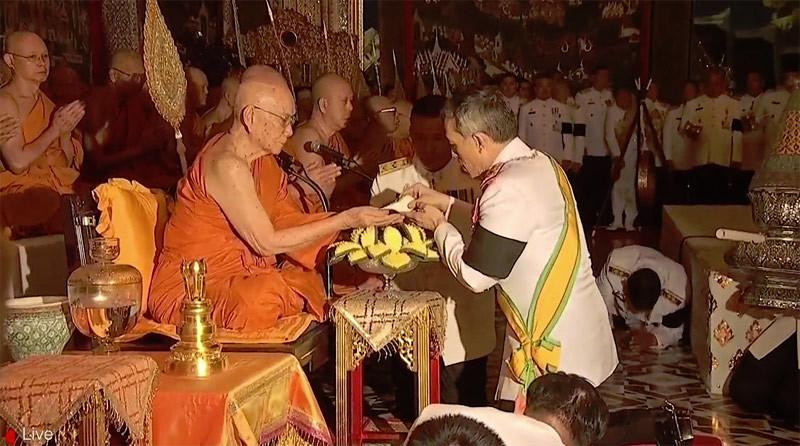 Raja Thailand Maha Vajiralongkorn (kanan) menuangkan air ke dalam telapak tangan Y.M. Somdet Phra Maha Muniwong dalam upacara pembasuhan di dalam rangkaian upacara penobatan Sangharaja Thailand Ke-20, Minggu (12/2/2017).