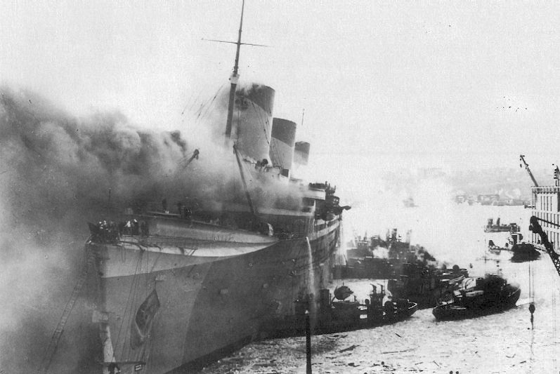 USS Lafayette, formerly SS Normandie, catches fire at Pier 88 in New York harbor, February 9, 1942.