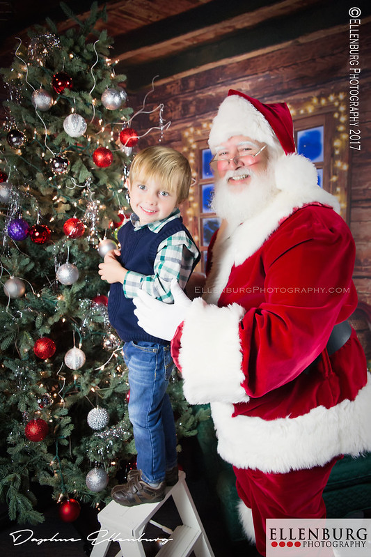 Boy decorating Christmas Tree with Santa