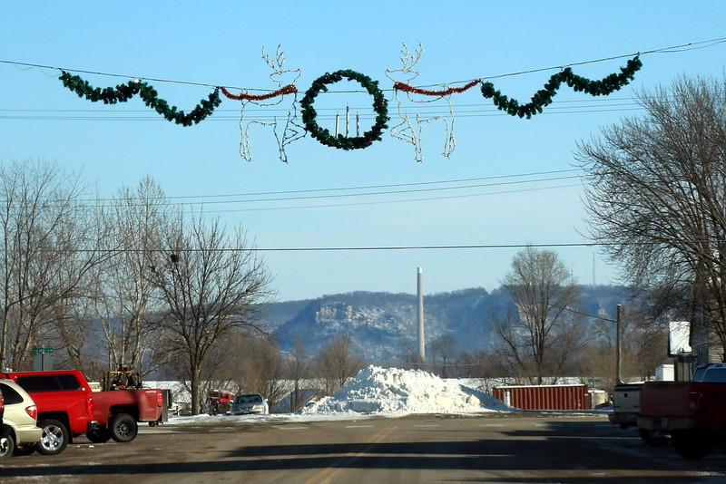 garland stretching across the street, with a wreath with three candles in the middle, and matching wire reindeer facing the center on both sides of the wreath