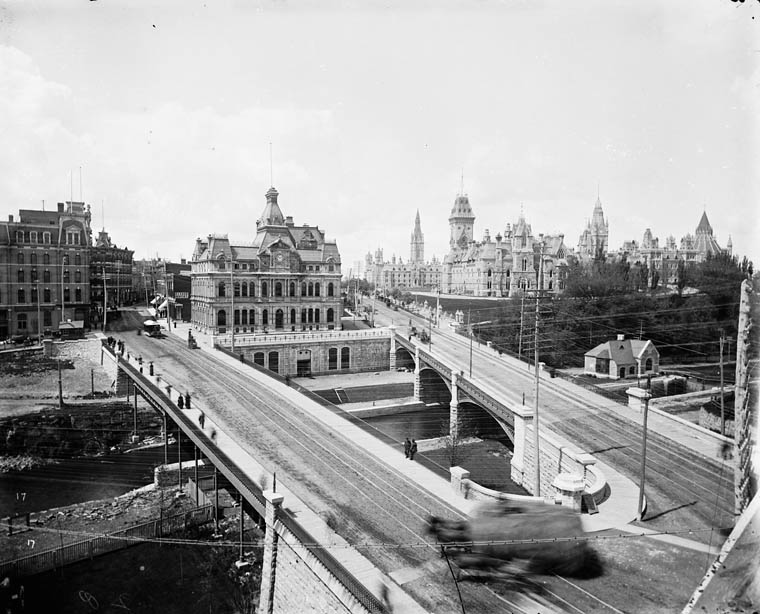 Old Ottawa Post Office. Sappers Bridge (left), Dufferin Bridge(right) over the Rideau Canal, 1890s. Today the War Memorial stands where the post office stood, with a new post office (now also old) on Sparks Street. The two bridges were replaced by the Plaza Bridge (Ottawa), and filled in.