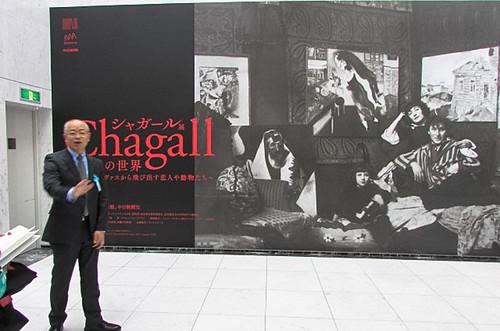 シャガール一家の写真パネルを前に説明する深谷克典副館長