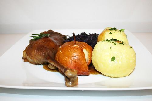 86 - Crispy goose legs with roast apple, red cabbage & filled potato dumplings . Side view / Knusprige Gänsekeulen mit Bratapfel, Rotkohl & gefüllten Kartoffelklößen - Seitenansicht
