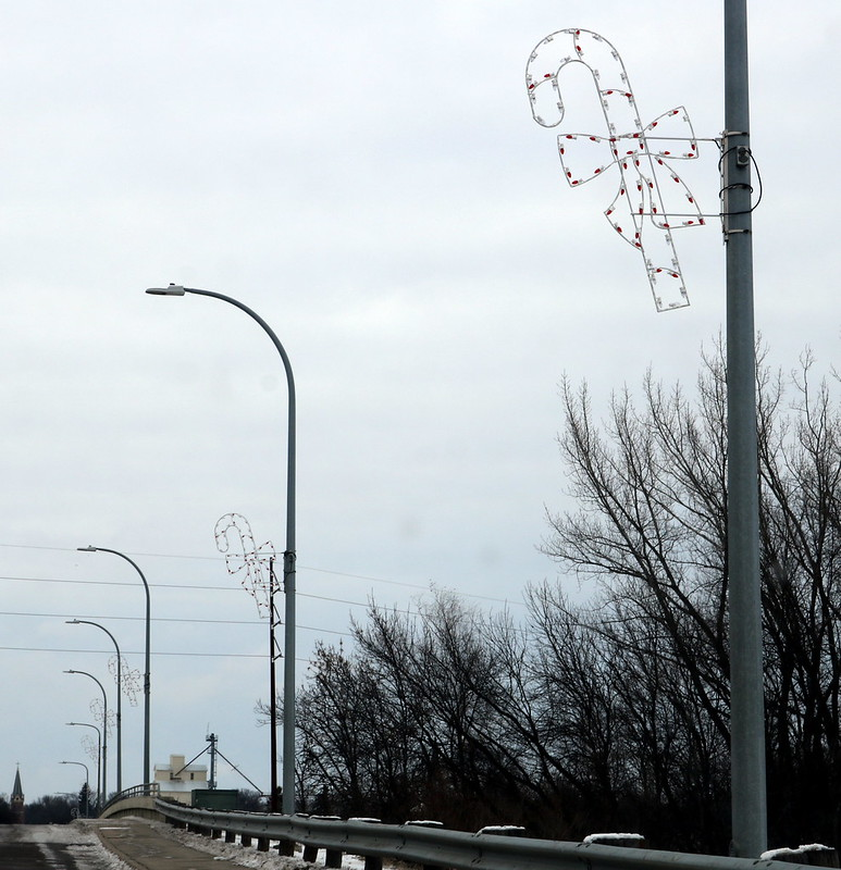 a white wire candy cane on a light pole at the top right, and four more in a diagonal row off into the distance