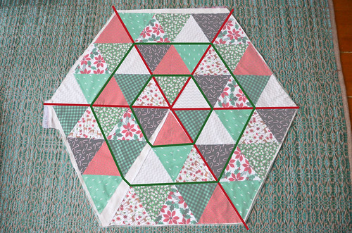 Quilting - I chose to quilt in red thread from the center, outward along the triangle edges. And then used green thread to sew the perimeter of the two hexagons.