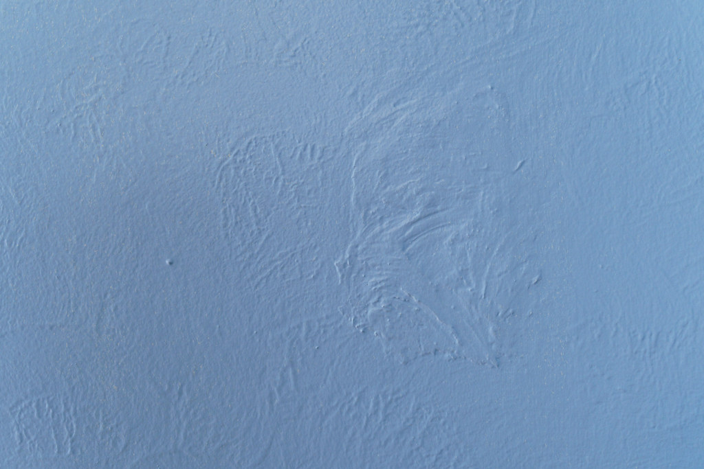 A close-up view of a wall where a light switch was long ago taken out and patched over