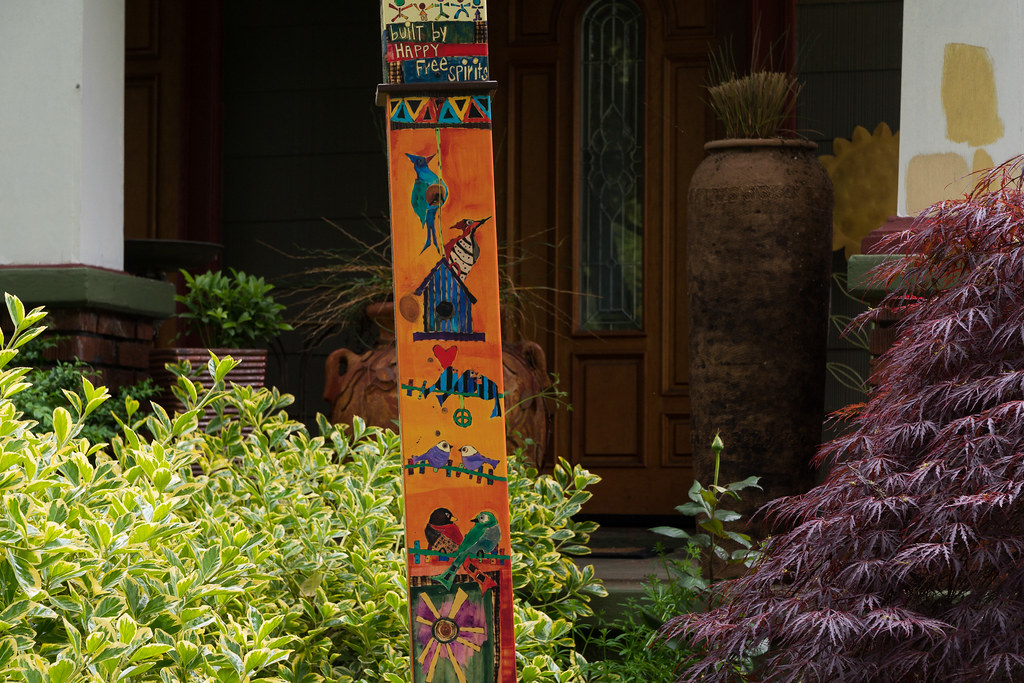 A pole painted with birds and the words 'built by happy free spirits' written at the top in a yard in the Irvington neighborhood of Portland, Oregon
