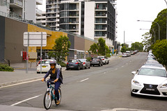 Bicyclist on street with apartment buildings, Rhodes, Sydney, Australia