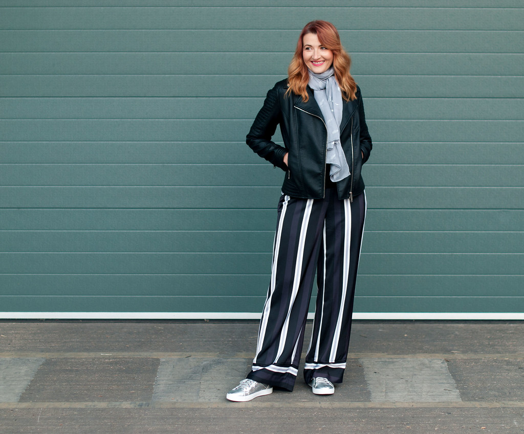 Winter to spring transitional outfit - Black biker jacket, wide leg stripe trousers, silver sneakers, grey scarf   Not Dressed As Lamb, over 40 style