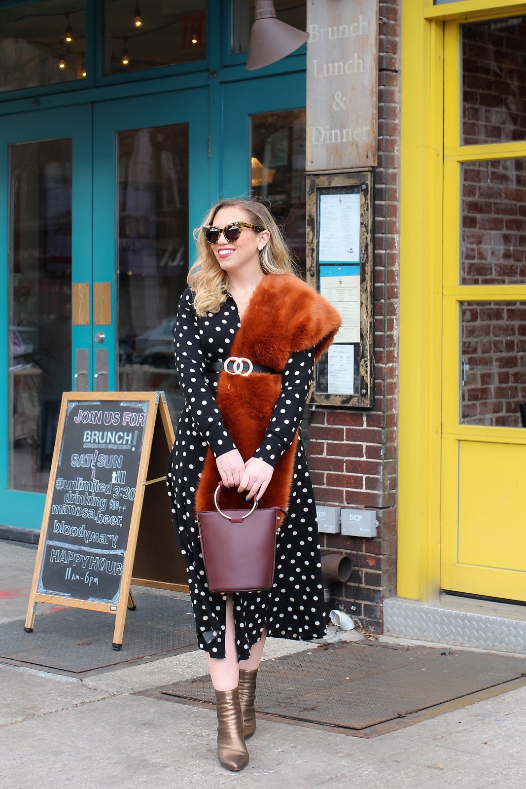 Blonde Girl Wearing Cat Eye Sunglasses Polka Dot Midi Dress Orange Faux Fur Scarf Pearl Belt Burgundy Ring Bag Bronze Booties