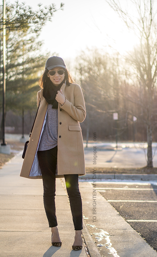 gray baseball cap, black infinity scarf, camel wool coat, black shoulder bag, black pants, leopard pumps, gray twist front top