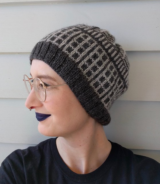 Woman's head in front of a weatherboard house. She wears a handknitted grey hat with Dalek colourwork motifs.