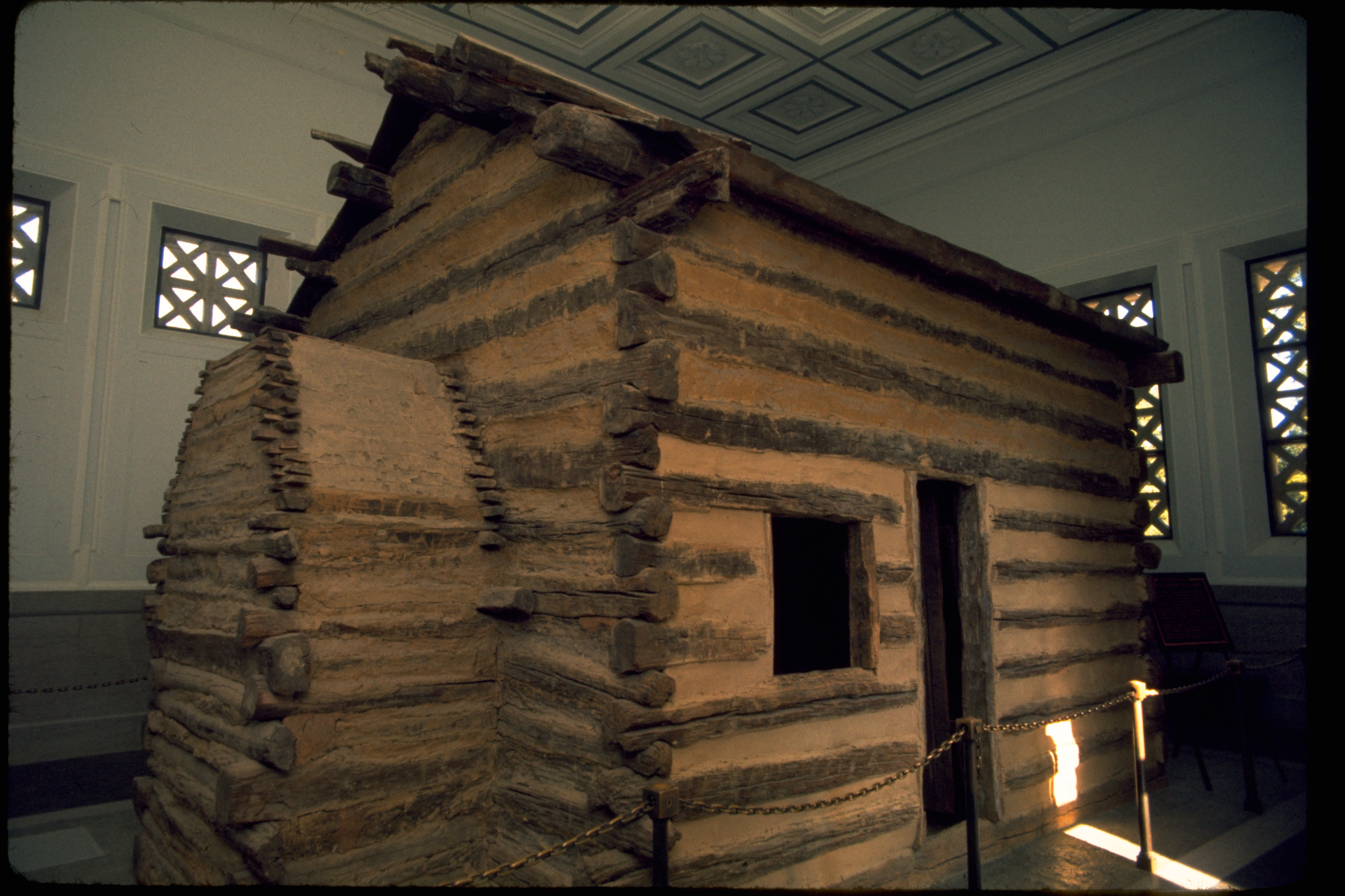 In the fall of 1808, Thomas and Nancy Lincoln settled on Sinking Spring Farm. Two months later on February 12, 1809, Abraham Lincoln was born there in a one-room log cabin. Today this site bears the address of 2995 Lincoln Farm Road, Hodgenville, Kentucky. A cabin, symbolic of the one in which Lincoln was born, is preserved within a 1911 memorial building at the site. The Memorial Building features 16 windows, 16 rosettes on the ceiling, and 16 fence poles, representing Lincoln being the 16th president. The 56 steps leading up to the building entrance represent his age at his death. The original log cabin that Lincoln was reputed to have been born in was dismantled sometime before 1865. Local tradition held that some of the logs from the cabin were used in construction of a nearby house.