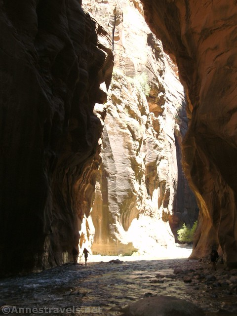 A hiker enters the shadows of the Zion Narrows in Zion National Park, Utah