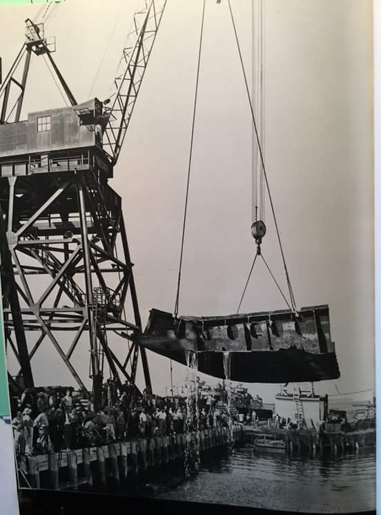 The last large piece of the former SS Normandie's keel is hoisted out of the water during scrapping operations at Port Newark, New Jersey, in late 1948.
