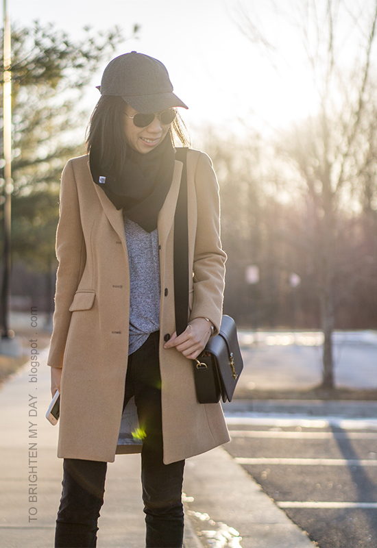 gray baseball cap, black infinity scarf, camel wool coat, black shoulder bag, black pants, gray twist front top