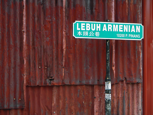 Street sign in front of a rusty corrugated metal wall in Penang, Malaysia