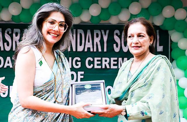 Aaliya Iqbal Naqvi of the Nasra School presenting a shield to Shahnaz Wazir Ali
