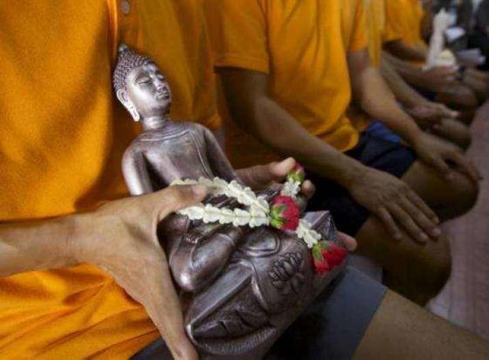 Seorang narapidana di Penjara Pusat Bang Kwang bersiap untuk memberikan salah satu rupaka Buddha kepada orang tuanya