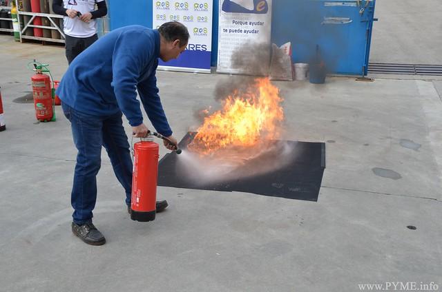 Un empresario participante apaga un fuego por medio de un extintor portátil.