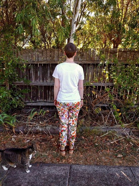 A woman stands in front of a garden fence. She wears sunnies, a white tee and tropical print slim fit pants. A cat is in the frame.