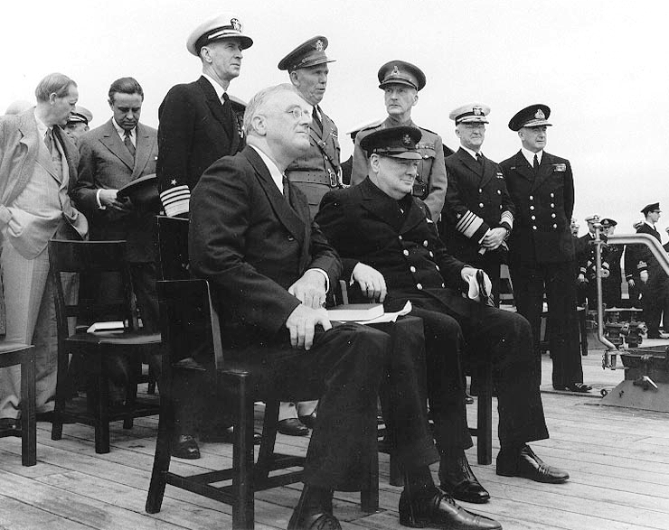Conference leaders during Church services on the after deck of HMS Prince of Wales, in Placentia Bay, Newfoundland, during the Atlantic Charter Conference. President Franklin D. Roosevelt (left) and Prime Minister Winston Churchill are seated in the foreground. Photo taken between August 10 and 12, 1941.