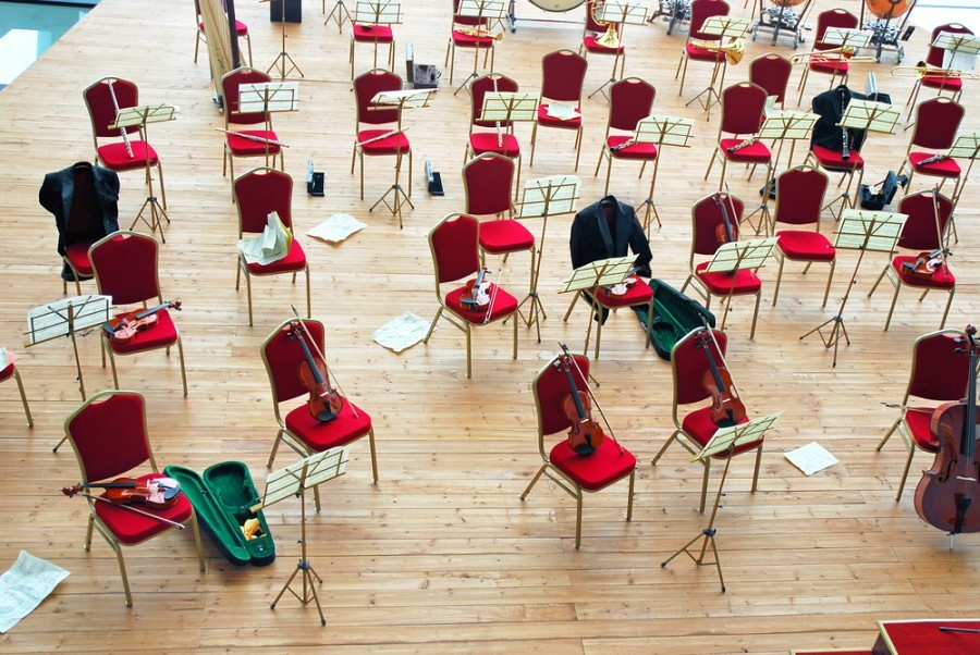 overhead shot of chairs and music stands arranged on a stage