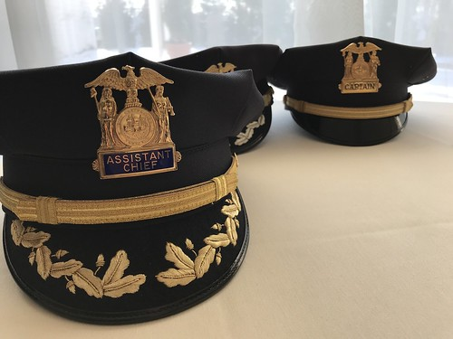Photo of Police Department hats placed on a covered tabletop