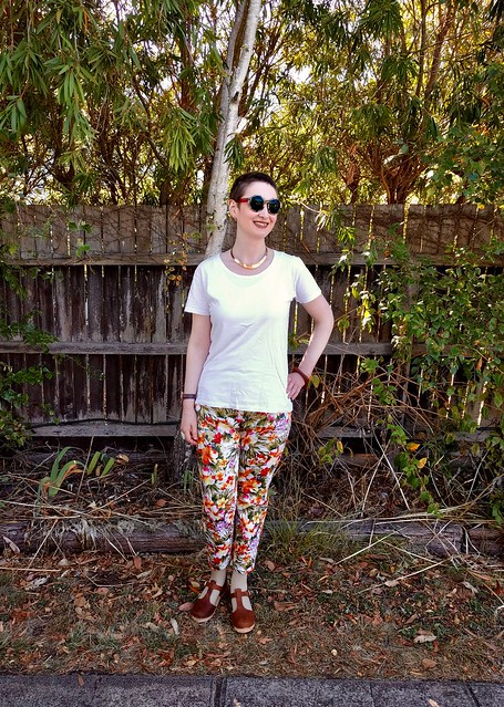 A woman stands in front of a garden fence. She wears sunnies, a white tee and tropical print slim fit pants.