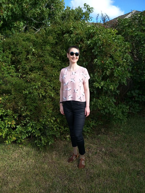 Woman stands in garden. She wears crane print pink woven tee, black coated skinny jeans, round tortoiseshell sunnies and tan clogs.