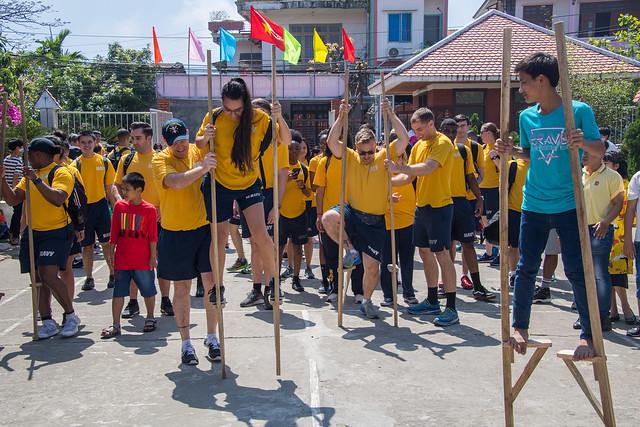 Sailors participate in stilt walking during a visit in Da Nang, Vietnam.